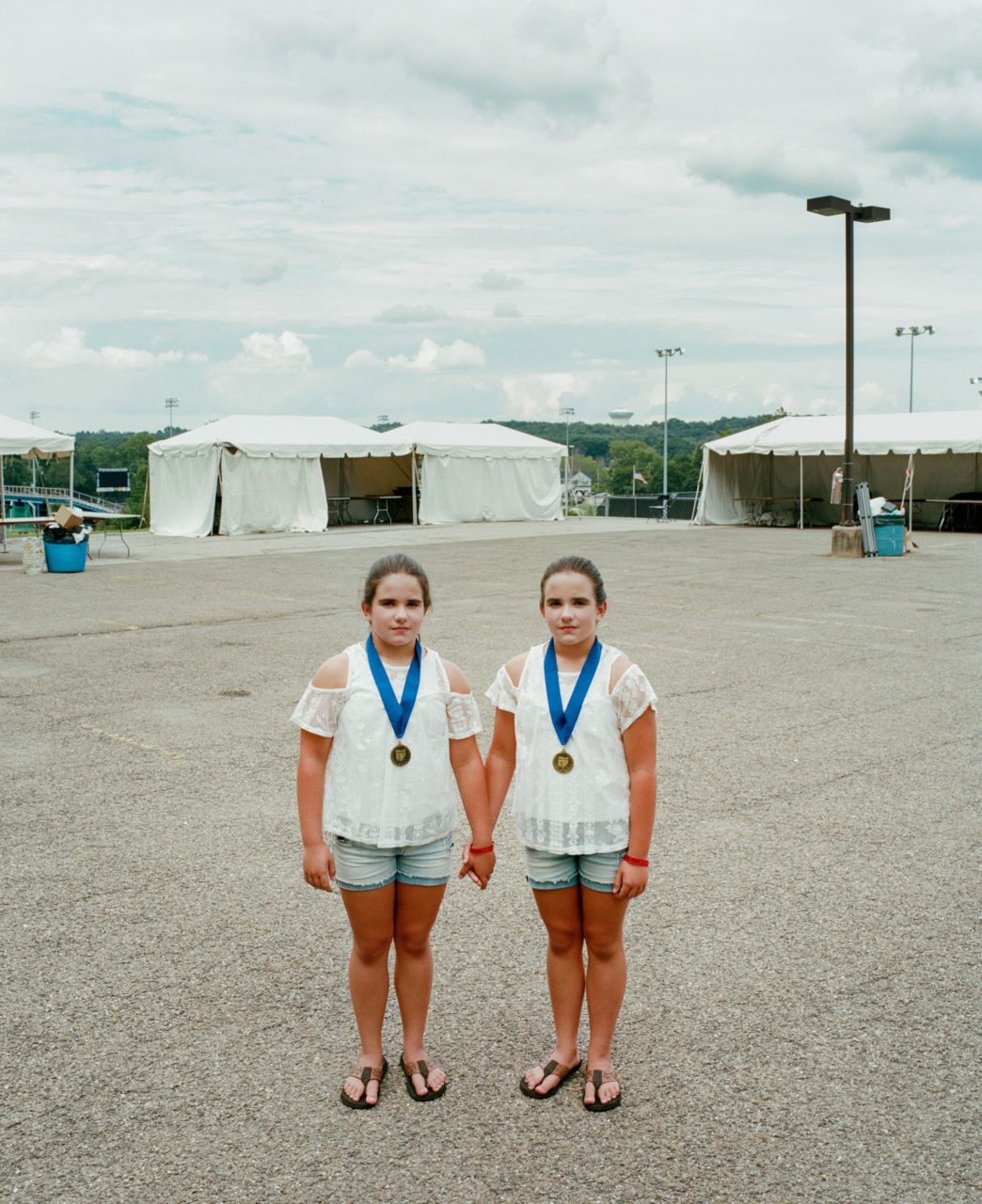 "Carlie and Rachel Knott, 10, of Somerset, Pa., have attended Twins Days every year since they were born. Their mother pointed out a mole on each of their necks, which at first appears identical, yet one is placed an inch forward than the other (see that on my Instagram). The pair donned medals from one of this year's ""most identical"" competitions at the festival (there is also ""least identical"" judging)."